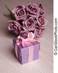 violet flowers and gift box with pink ribbon