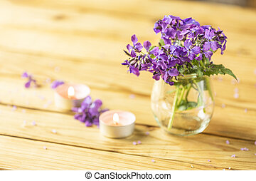 Violet flowers in glass jar and perfumed candle on natural ...