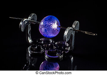 Violet glass bead on stand on black background