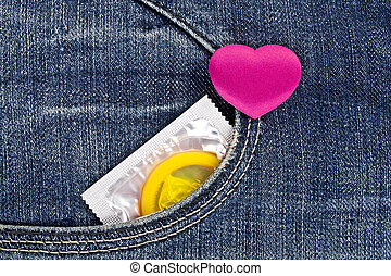 Violet heart and yellow condom in blue jeans pocket