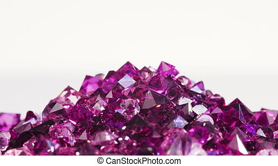 Violet jewel stones heap turning over white background, loop...