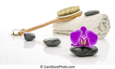 Violet orchid with spa stones, brush and towel