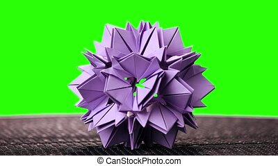 Violet origami flower on green screen. Spiky origami model...