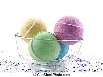 Violet salt and multicoloured bath balls in glass bowl