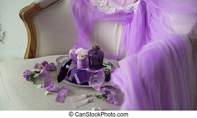 Violet tray with bottle, jewelry ring and lingerie on chair