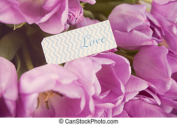 Violet tulips and note with word love.