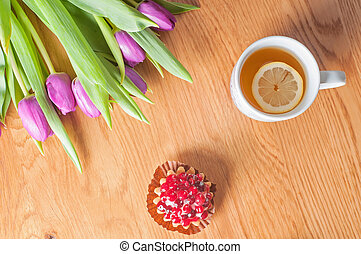 Violet tulips, cake and tea on the wood