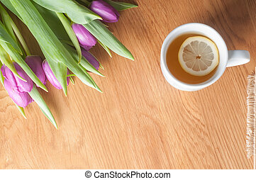Violet tulips on the wood and tea, top view