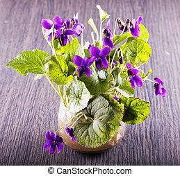 Violets in a vase over wooden table, horizontal image