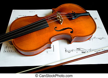 Violin and a Bow on a Music Sheet - This is a close-up of a...