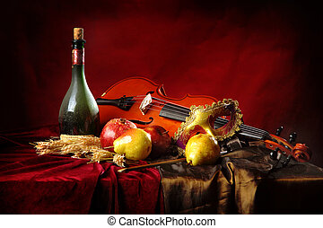 Violin and Masquerade Mask on a red background next to a bottle of old wine and fruit