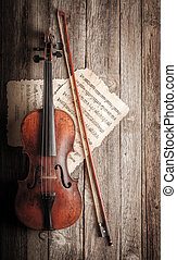 Violin, bow and musical score on wooden background
