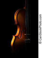 Violin detail on a black background between light or shadows