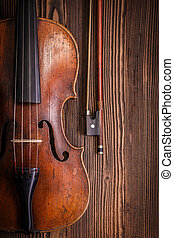 Violin detail with bow on wooden background