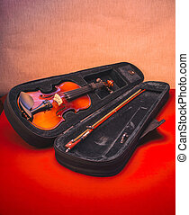 Violin in an open case on a red table