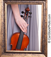 violin in hand of a young woman seen through a frame