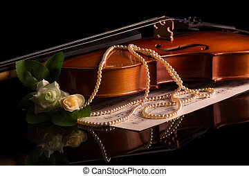 Violin lies on the table, next to musical notes isolated on black