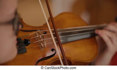 Violin music violinist playing while holding an instrument in hand. Person masterfully plays string during concert. Man performs musical composition at music festival. View of wooden classical musical instrument during rehearsal.
