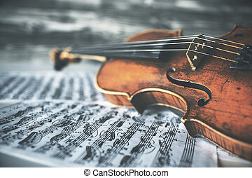 Violin on music sheets - Closeup of vintage violin placed on...
