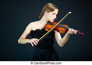 Violin performance - Portrait of a young female playing the...