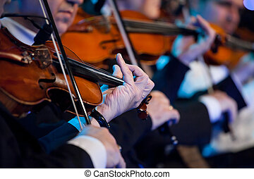 Violin players close up during a classical concert music