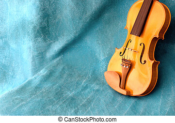 violin resting against blue background with copy space