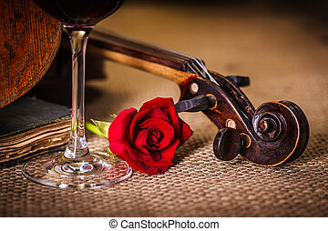 Violin scroll close with red rose