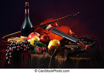 Violin with a bow on a red background next to a bottle of old wine and wet fruit