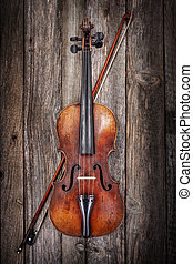Violin with bow on wooden background