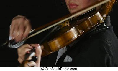 Violinist girl bows the violin strings. Clos up. Black smoke background