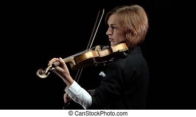 Violinist holds a bow plays a lyrical work. Black background...