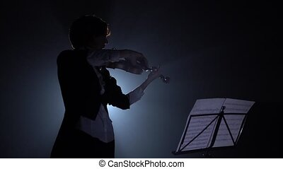 Violinist looks at the notes and plays . Silhouette. Black smoke background