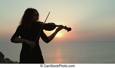 Violinist on the background of an incredibly beautiful sunset on the sea