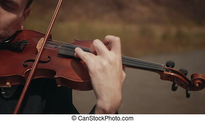 Violinist on the bridge, street Performer playing violin, outside. Close-up