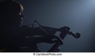 Violinist performing in a dark studio with a lantern. Black background. Silhouette