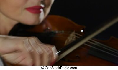 Violinist performs on a violin in a black smoke studio. Close up