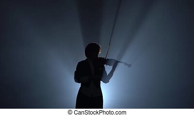 Violinist performs on a violin in a black smoke studio. Silhouette. Black smoke background