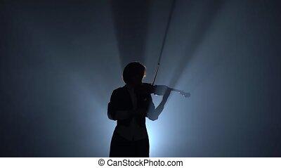 Violinist performs on a violin in a black smoke studio....