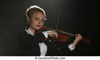 Violinist performs on a violin in a black smoke studio -...
