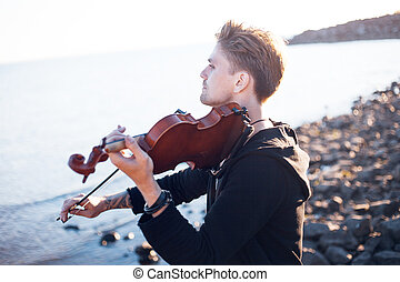 Violinist playing a violin, young man plays on the...