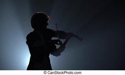 Violinist plays a lyrical work. Black smoke background. Close up. Silhouette