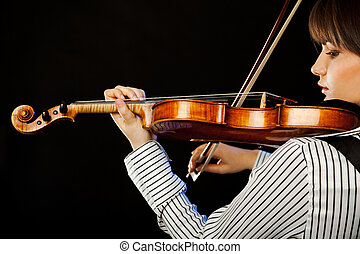 Beautiful female musician playing violin profile isolated on black