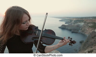 Violinist stands on the cliff on the sea and plays -...