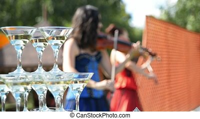 violinists playing on the background wine glasses with champagne