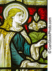 Victorian stained glass window showing the Virgin Mary at the Annunciation from the Angel Gabriel. Historic window on public display over 100 years.