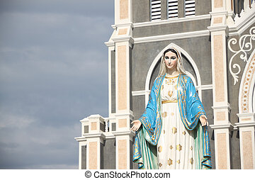 Virgin mary statue in front of church.