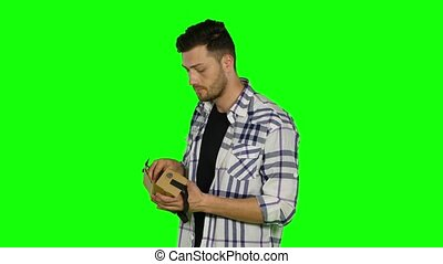 Virtual reality game. Boy uses head mounted display. Green screen