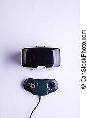 Virtual reality goggles and gamepad on table, studio shot -...