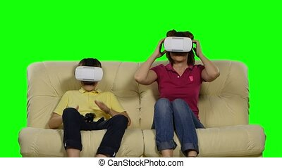 Virtual reality mask. Young mother and her son with pleasure...