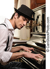 Virtuoso playing piano. Side view of handsome young man playing piano